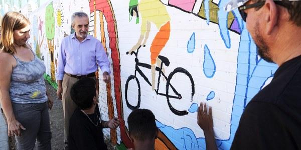 (11/9/2017)  El Ayuntamiento completa la reurbanización de la Plaza Santa Teresa de Jesús del Distrito Cerro-Amate con un mural pintado por jóvenes del barrio
