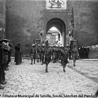 Puerta del León. Desfile de las Fuerzas Regulares Indígenas, creadas en Marruecos en 1911. En el interior, aún perduran las edificaciones que tapiaban los arcos y parte del lienzo de muralla. 1920-1922 ©ICAS-SAHP. Fototeca Municipal de Sevilla, fondo Sánchez del Pando