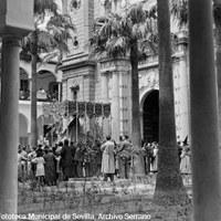 9. JUAN JOSÉ SERRANO GÓMEZ.La Esperanza Macarena hace su entrada en la iglesia del Hospital de las Cinco Llagas. 1938. Entre 1937 y 1940 la cofradía salía de la iglesia de la Anunciación y se recogía en este centro hospitalario debido al incendio de su sede en la parroquia de San Gil en 1936. Entre el público, los sanitarios con batas blancas y los enfermos, heridos de guerra, asomados en la balconada de la primera planta. © ICAS-SAHP, Fototeca Municipal de Sevilla, Archivo Serrano