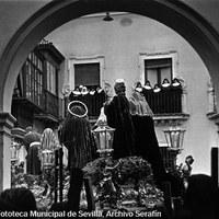 25. SERAFÍN SÁNCHEZ RENGEL. Salida del misterio del Cristo de la Caridad en el Traslado al Sepulcro desde la iglesia de San Andrés. 1963.  Desde los balcones que dan a la plaza de San Andrés, las hermanas de la congregación de las Siervas de María admiran el sobrecogedor grupo escultórico de Ortega Bru.   © ICAS-SAHP, Fototeca Municipal de Sevilla, Archivo Serafín