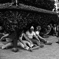 """29. JUAN JOSÉ SERRANO GÓMEZ. Un descanso entre chicotás. 1966.  Los hombres del costal descansan bajo la impresionante canastilla neobarroca barnizada en caoba de la Hermandad de la Carretería. Con la irrupción de los hermanos costaleros en 1973 la profesionalidad tiende a desaparecer. La primera cuadrilla no profesional fue la del paso del Cristo de la Buena Muerte de los Estudiantes, mandada por Salvador Dorado """"El Penitente"""".  © ICAS-SAHP, Fototeca Municipal de Sevilla, Archivo Serrano"""