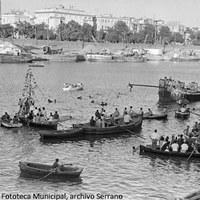 9. Las embarcaciones se arremolinan junto a la barcaza de la cucaña. Al fondo, el Muelle de la Sal en plena actividad portuaria. 1964. ©ICAS-SAHP, Fototeca Municipal, archivo Serrano.