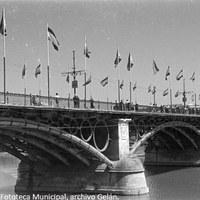 19. Puente de Isabel II a punto para los días de la Velá. En estos años el puente se engalanaba desde el 16 de julio con motivo de la procesión fluvial de la Virgen del Carmen. 1969. © ICAS-SAHP, Fototeca Municipal, archivo Gelán.