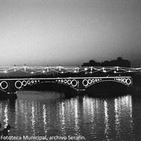 25. El Puente de Triana, otro de los símbolos de la Velá, reflejado en el Guadalquivir. Década de 1970.  ©ICAS-SAHP, Fototeca Municipal, archivo Serafín.