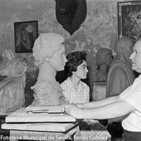18.- El escultor e imaginero Antonio Illanes Rodríguez en su estudio modelando una obra con la  modelo de su inspiración al fondo. 1967. ©ICAS-SAHP, Fototeca Municipal de Sevilla, fondo Cubiles