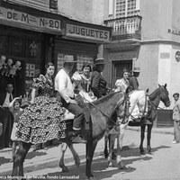 Caballistas con flamencas a la grupa se dirigen al Real. Posan en la calle Bailén esquina con Pedro del Toro, ante la juguetería de Vda. de Martínez. 1935 ca.
