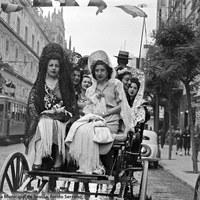 Ataviadas con mantones y mantillas se dirigen al Real en un coche de colleras por la avenida de José Antonio (hoy Constitución). A la izquierda, un tranvía junto a la Punta del Diamante y a la derecha un dispensador de gasolina. Década de 1940.