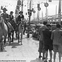 En el Real transitan los caballistas entre las hileras de automóviles. Los chicos lucen pantalones cortos, propios de la edad y la moda de estos años. 1945 ca.