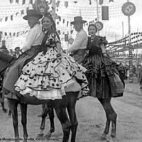 Parejas de caballistas en la Feria. Una de las mujeres luce en el peinado unos elaborados caracolillos. 1945 ca.