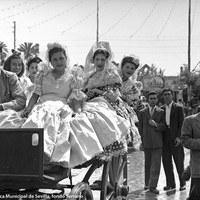 En coche de punto, varias jóvenes posan para el reportero en una Feria de 1950. A la derecha, la caseta de la peña El Chachi.