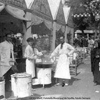 Casetas de buñoleros y buñoleras, con camareros uniformados, en una Feria hacia 1928.