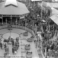 """Feria de 1942. Atracciones, barracas y tenderetes en la """"calle del infierno"""". El látigo, los coches de choque, la barraca La Carcajada y las tómbolas reúnen a personas de toda clase o condición."""