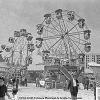 """La """"calle del infierno"""" en la Feria de 1968. Destacan las dos norias instaladas en la Huerta de la Salud. Detrás, pisos en construcción de la avenida de la Borbolla."""