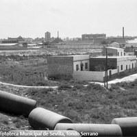 11. Barriada de El Turruñuelo, 1964. Las calles del Turruñuelo fueron adoquinadas en 1940 y rotuladas en 1950. Pero no fue hasta mediados de los años sesenta cuando se acometieron obras de saneamiento e infraestructura. En el horizonte, la fábrica de espejos y cristales de Pueyo y las chimeneas de los tejares que compiten en altura con la Torre de Los Remedios.  ©ICAS-SAHP. Fototeca Municipal de Sevilla, fondo Serrano