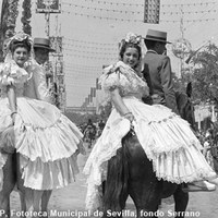 Mujeres vestidas de flamenca y adornadas con mantillas, pasean a la grupa por la Feria. 1948  ©ICAS-SAHP, Fototeca Municipal de Sevilla, fondo Serrano