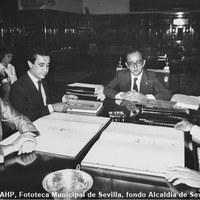 22.- El alcalde Manuel del Valle presenta un avance del PGOU a la oposición municipal. A la izquierda, Javier Arenas (PP) y Javier Aristu (PCE). 1985 ©ICAS-SAHP, Fototeca Municipal de Sevilla, fondo Alcaldía de Sevilla