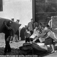 16. Las familias afectadas, como estos vecinos de La Corza, retiran camas, colchones y otros enseres suministrados por la Junta de Trabajo y Reparto. 11 de diciembre de 1961 ©ICAS-SAHP, Fototeca Municipal de Sevilla, archivo Gelán